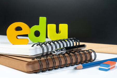 Classic school background with wooden word EDU for education. Education school background concept with equipment pen, pencil, book, backboard and copyspace.