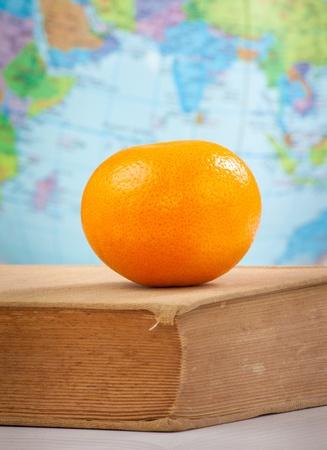 Orange on old book on globe background photo