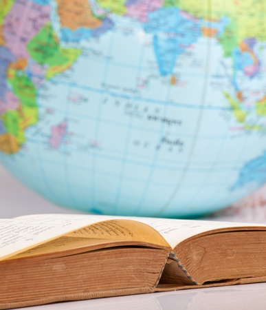 Open old book on globe background photo