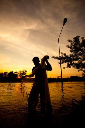 silhouette of fishermen fishing net on sunset photo