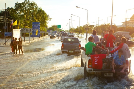 worst: AYUTTHAYA - OCTOBER 9,2011: Pickup truck transporting flood victims through the streets of the city during the worst monsoon flood. October 9, 2011 in Ayutthaya, Thailand.