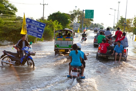 AYUTTHAYA - OCTOBER 9,2011: Pickup truck and motorcycle transporting flood victims through the streets of the city during the worst monsoon flood. October 9, 2011 in Ayutthaya, Thailand.