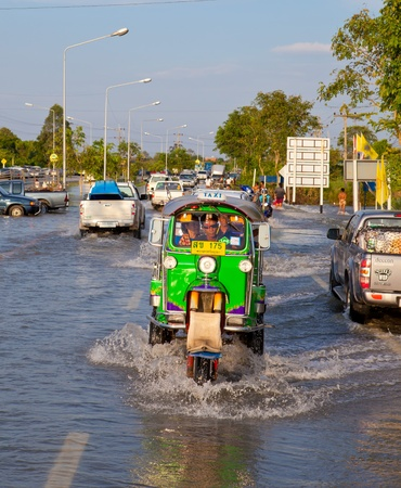 AYUTTHAYA - OCTOBER 9: Pickup truck and motorcycle transporting flood victims through the streets of the city during the worst monsoon flood. October 9, 2011 in Ayutthaya, Thailand.