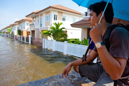BANGKOK - OCTOBER 24, 2011:  Man looking own house in flooded during the monsoon season  of October 24, 2011 in Bangkok,