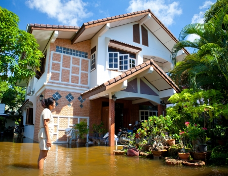 AYUTTHAYA - OCTOBER 9, 2011:  Women looking own house in flooded during the monsoon season of October 9, 2011 in Ayutthaya, Thailand. 新聞圖片