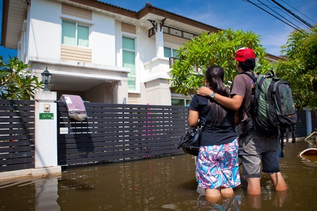 BANGKOK - OCTOBER 24, 2011: The Couple looking own house in flooded during the monsoon season of October 24, 2011 in Bangkok, Thailand.