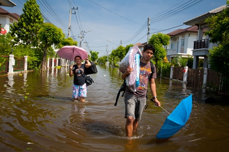 BANGKOK - OCTOBER 24, 2011: People wading through the streets of the city during the worst monsoon flood of October 24, 2011 in Bangkok, Thailand.