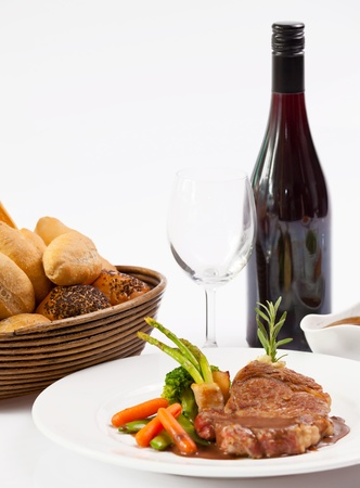Grilled steak , wine and bread on white background photo