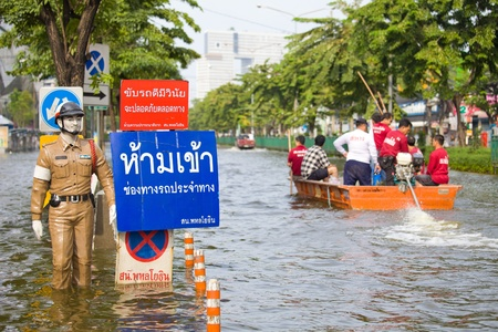 BANGKOK, THAILAND - NOVEMBER 5, 2011 : Police puppet standing on flood hits Central of Thailand, higher water levels expected, cars navigating through the flood on November 5,2011 Bangkok, Thailand. Stock Photo - 11109387