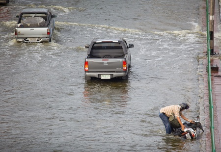 BANGKOK, THAILAND - NOVEMBER 5 : motorcycle accident of a man on flood hits Central of Thailand, higher water levels expected, cars navigating through the flood on November 5,2011 Bangkok, Thailand.