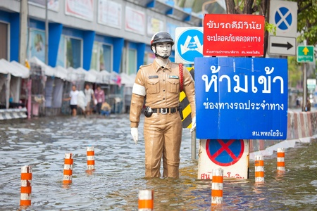 BANGKOK, THAILAND - NOVEMBER 5, 2011 : Police puppet standing on flood hits Central of Thailand during the worst flooding in decades on November 5,2011 Bangkok, Thailand. Stock Photo - 11116806
