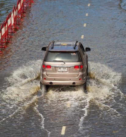 expected: BANGKOK, THAILAND - NOVEMBER 12,2011 : Thai flood hits Central of Thailand, higher water levels expected, cars navigating through the flood on November 12,2011 Bangkok, Thailand.