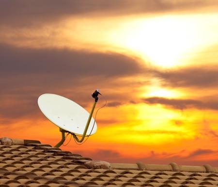 Antenne parabolique avec le coucher du soleil sur le toit