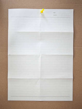 paper sheet and pin on wood texture background photo