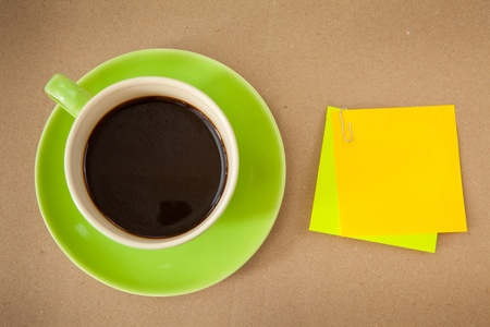 green cup of hot coffee and note paper on wood background photo