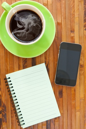 green cup of hot coffee smartphone and book on wood background photo