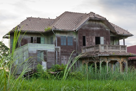 damaged roof: abandoned architecture old wood house in Thailand
