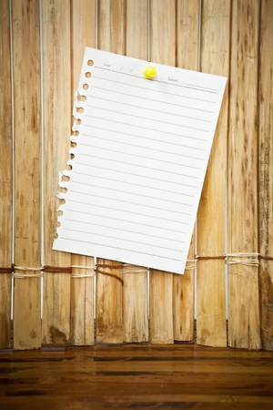 paper sheet and red pin on wood texture background photo