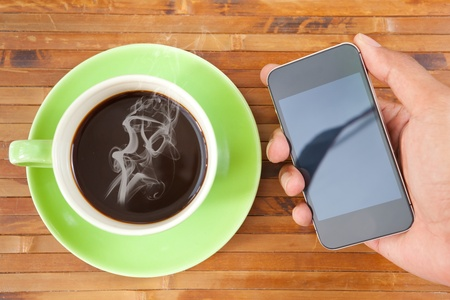 green cup of hot coffee smartphone on wood background