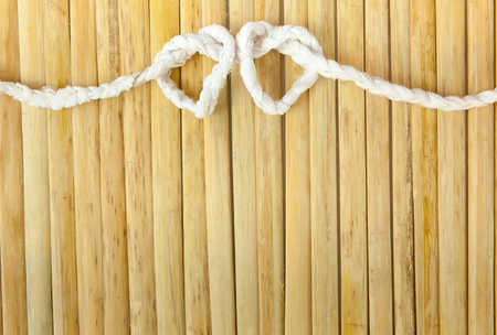 Rope in the shape of heart isolated on wood background photo