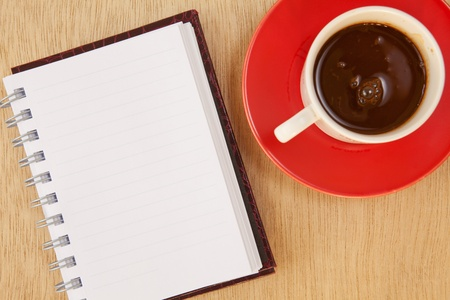 cup of hot coffee and book on wood background photo