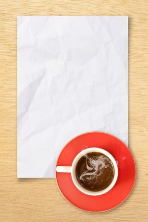 cup of hot coffee and note paper on wood background photo