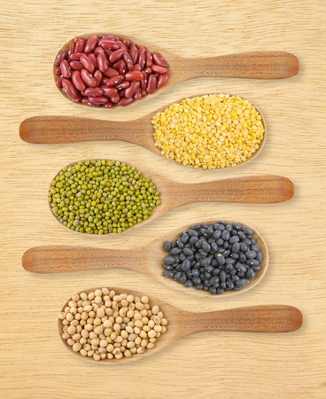 collection of beans on wooden spoons on wood photo
