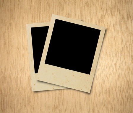 Blank photos frames on wood background photo