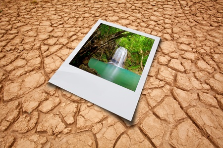 Dry cracked earth background and waterfall picture photo