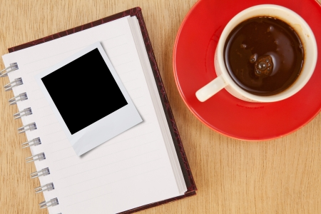 cup coffee and photo frame and notebook on wood background photo