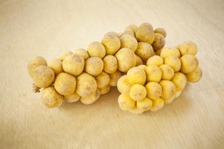 Tropical fruit langsat on wood background photo