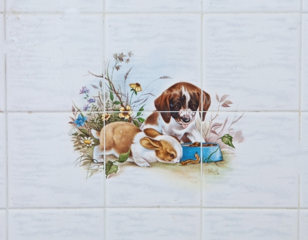 decorative tile with dog and rabbit design photo