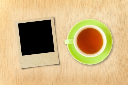 cup tea and photo frame on wood background photo