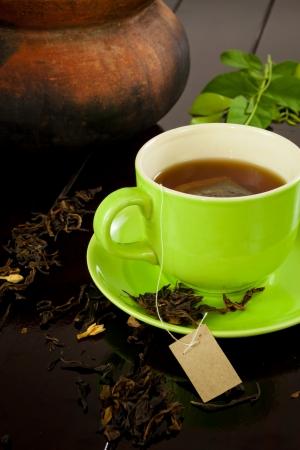 ウッドの背景で熱いお茶の緑カップ