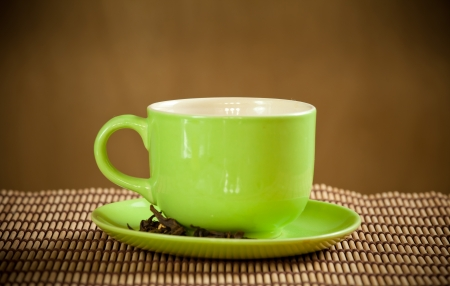 green cup of hot tea on wood background photo