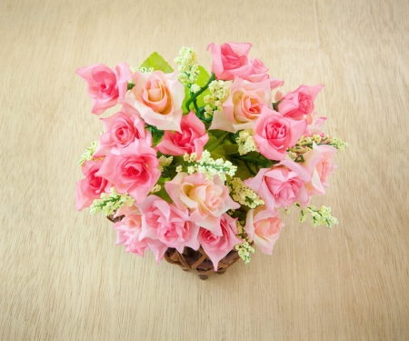 Wood basket roses isolated on wood background photo