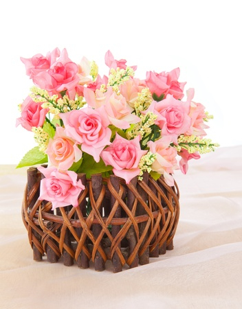 Roses in wood basket on fabric pink background photo