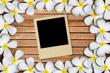 Blank photo frame on wood and flower background photo