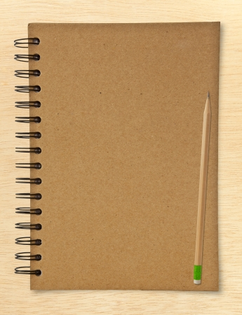 ring binder: recycle notebook and wooden pencil on wood background
