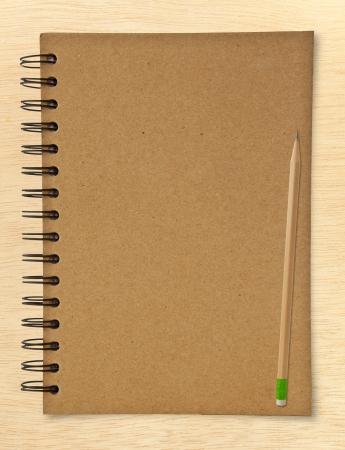 recyclen notebook en houten potlood op hout achtergrond