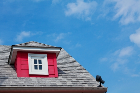 red dormer on the roof of a wood home photo