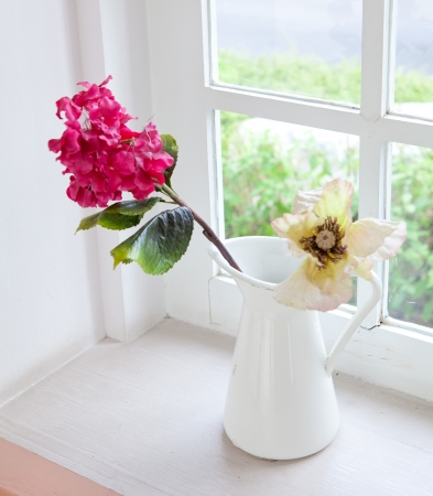 white vase and flower on the white table photo
