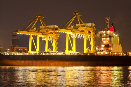 Industrial shipping port at night in Bangkok, Thailand photo