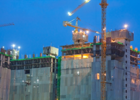 industrial site: Industrial construction cranes and building at night