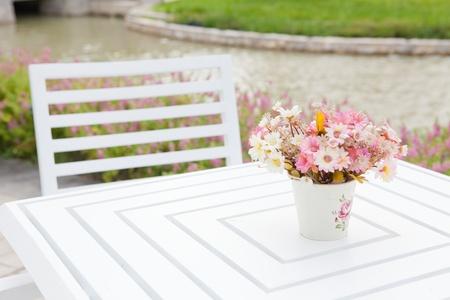白い花瓶や白いテーブル上の花