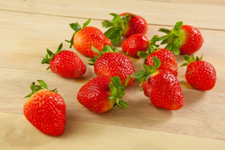 Red strawberries on old wood table photo