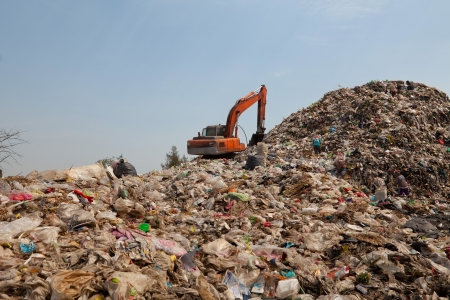 Backhoe moves trash in a landfill site, pollution, Global warming Imagens - 18236158