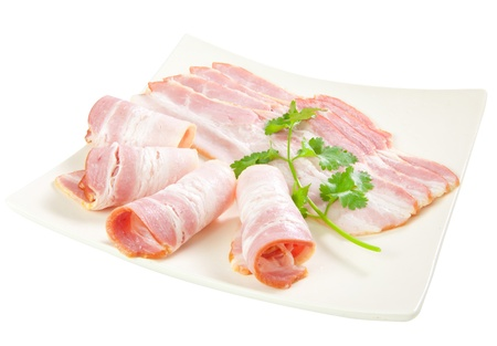 bacon fat: Tasty sliced bacon with vegetables isolated on white background Stock Photo