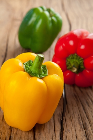 three sweet peppers, wooden table background photo
