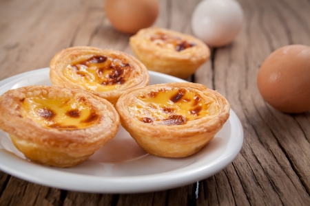 delicious portuguese egg tart on wood background Imagens